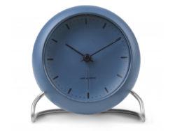 Arne Jacobsen City Hall bordur i blå og er lavet af plast. Foden er lavet i mat stål. Borduret er med alarm og LED lys. Urets diameter er 11 cm. Arne Jacobsens bordur passer godt til boligindretningen, på en hylde eller på kontoret.